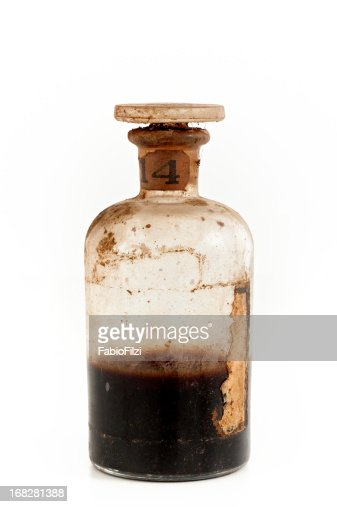 An old glass bottle half filled with brown poison