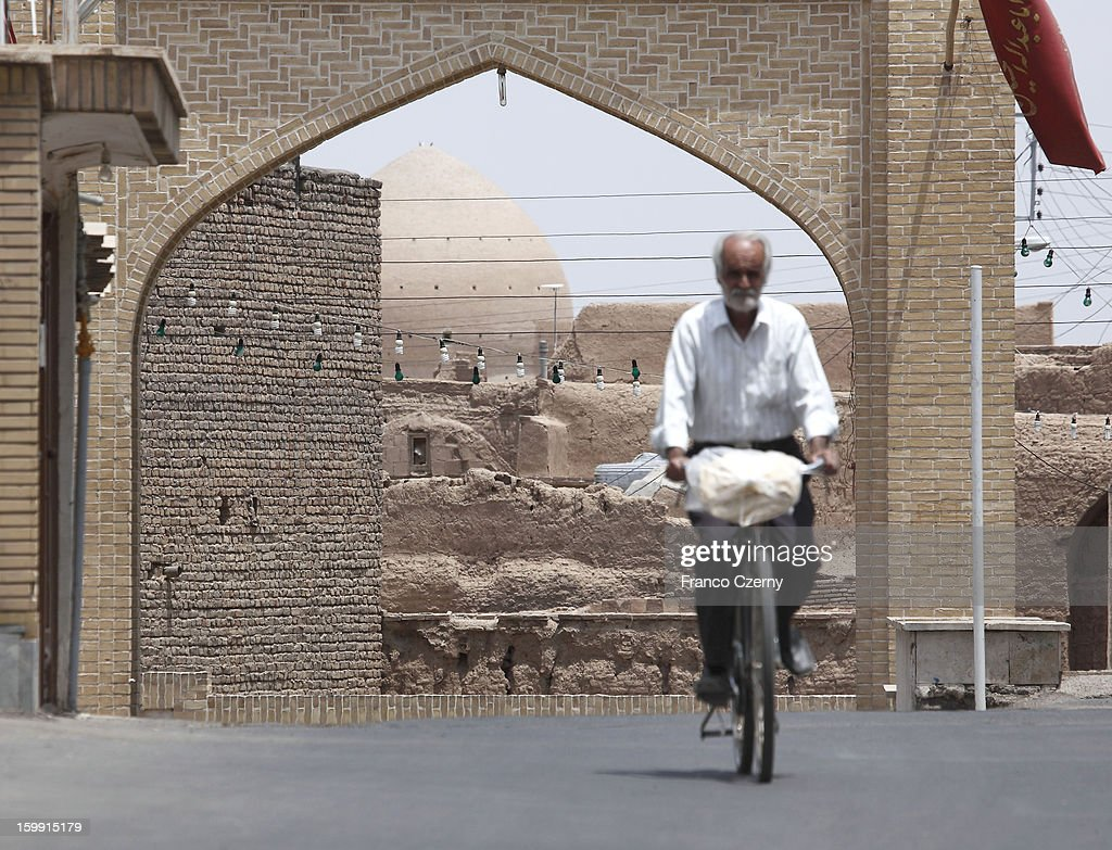 An old iranian man rides his bicycle, Agha Bozorg mosque in background on August 15, 2012 in Kashan, Iran.