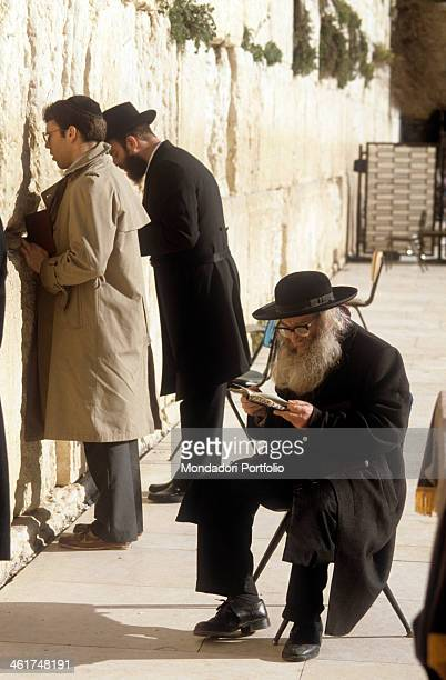 An old jewish pilgrim with a long gray beard sits by the Wailing Wall committed in reading the Torah in total contemplation while two others younger...