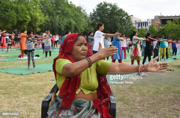 An old lady practice an Yogic Posture during the Mass Yoga Practice organised on International Yoga Day at National Institute of Ayurveda on June 21...