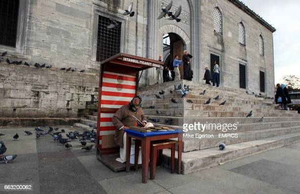 An old lady sells bird seed to the tourists to feed the pigeons outside the New Mosque