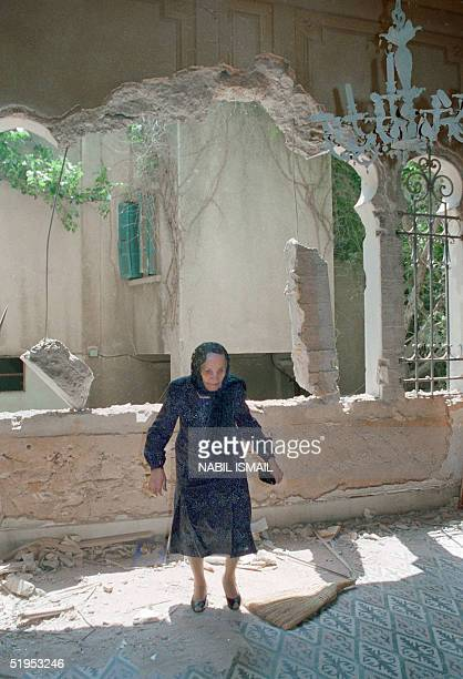 An old Lebanese woman inspects 09 May 1989 the damages in her house in Moslem west Beirut during a break in the fighting between Syrian troops Amal...