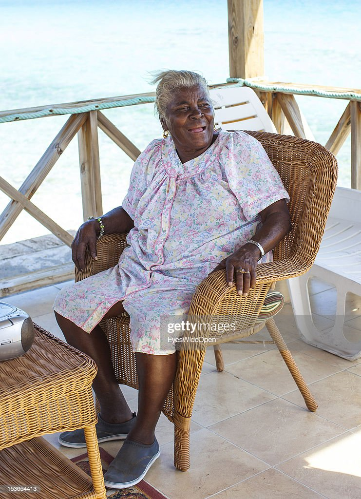 An old local bahamian woman sitting in a chair at the beach on June 15, 2012 in Cat Island, The Bahamas.