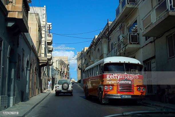An old Maltese bus rattles along the road of Valetta.