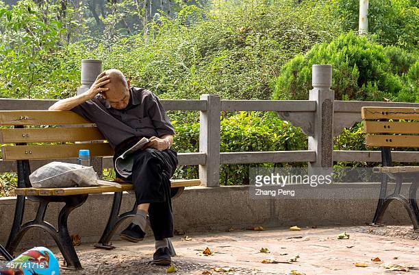 An old man alone reads a magazine in a public park In China there are more than 200 million old people of over 60 years old at present which accounts...