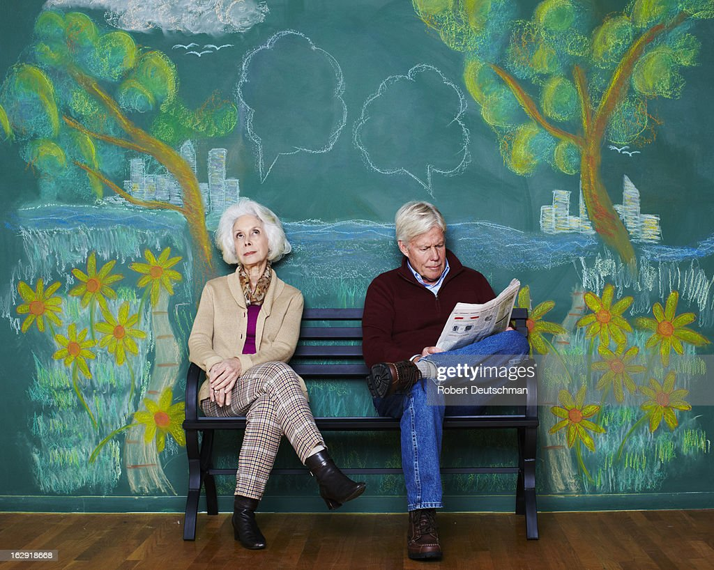 An old man and woman sitting on a park bench. : Stock Photo