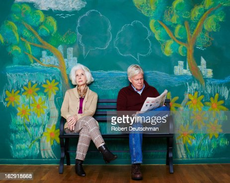 An old man and woman sitting on a park bench.