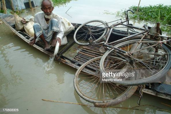 an-old-man-bailing-water-from-a-boat-in-the-flood-affected-area-21-picture-id170503325?s=594x594