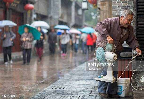 An old man brings his old styled electronic fan into his private operated store in ancient Dongguan street In China there are more than 200 million...