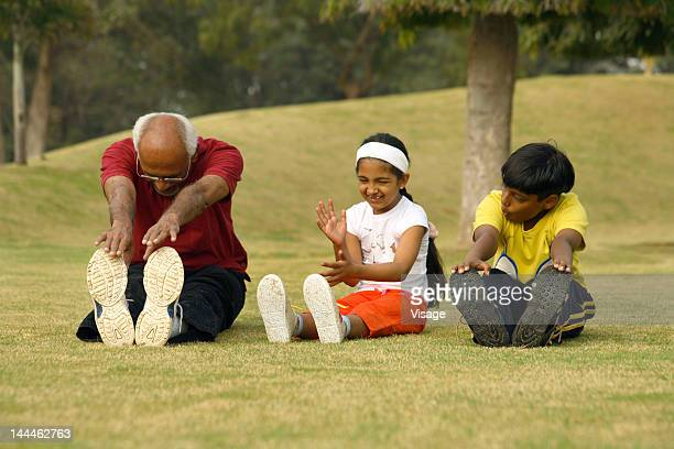 An old man exercising with his grandchildren in a park