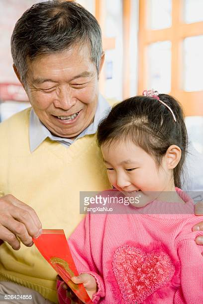 An Old Man Giving Red Packet to Little Girl
