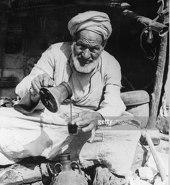 An old man in Iraq pours tea in the sunshine