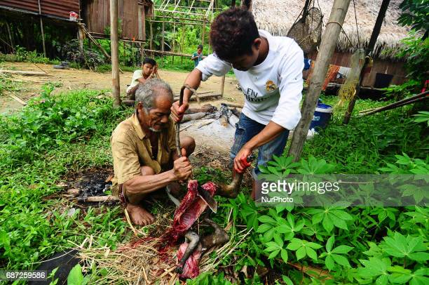 An old man of Che Wong Mahani cut the silvery lutung into pieces with the help of Che Wong young boy in a rural village in Malaysia on 23 May 2017...