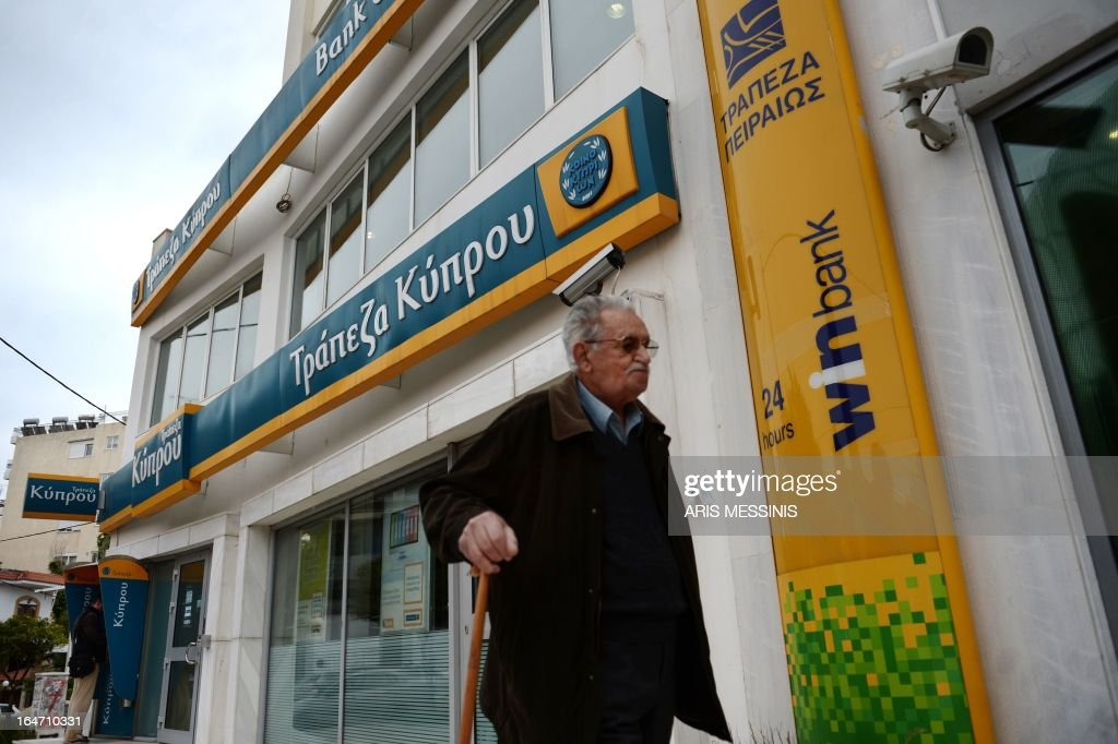 An old man passes by a Bank of Cyprus branch in Athens on March 27, 2013, as Greek subsidiaries of three Cypriot banks reopened today after Greece's third lender, Piraeus bank, signed an agreement to acquire all their deposits, loans and branches. But banks in Cyprus itself remained closed as authorities worked out a plan to get them back up and running amid the country's financial crisis.