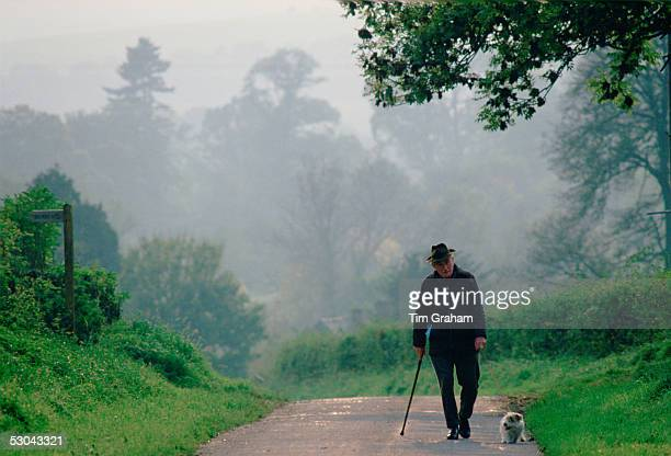 An old man walking his dog in a quiet country lane in Wiltshire England