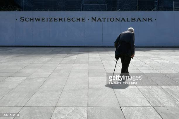 An old man walks past a sign of the Swiss National Bank in front of its building curently in renovation on Juin 15 2017 in Bern The Swiss National...