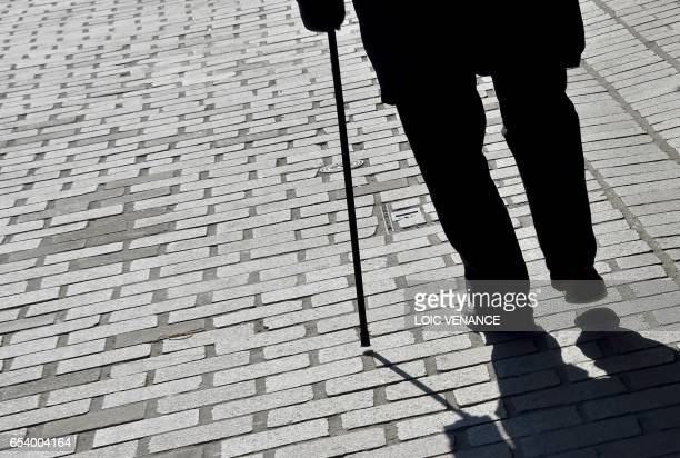 An old man walks with a cane on March 16 2017 in Nantes western France / AFP PHOTO / LOIC VENANCE