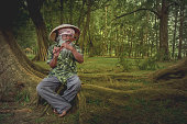 An old man from Malaysia is playing a flute in the forest
