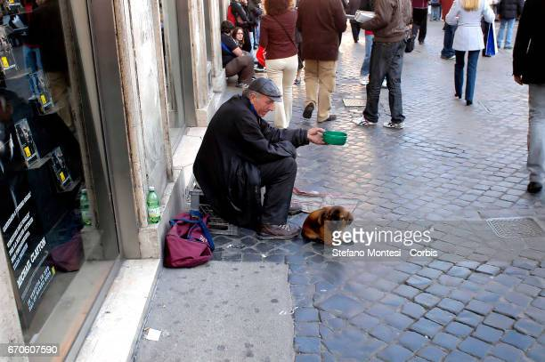 An old man with a dog begsin Largo Argentina on March 29 2008 in Rome Italy