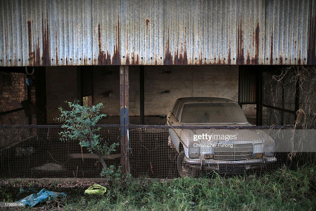 An old Mercedes car and buildings deteriorate and become overgrown with vegetation at the old 17 shaft mine at Crown Mines on July 16, 2013 in Johannesburg, South Africa. Johannesburg became the centre of gold mining in 1886 when gold was first discovered. Two government officials were sent to establish a settlement and named it Johannesburg after the first name they both shared. The gold rush lasted for over 100 years. The South African mining industry has shed more than 340,000 jobs since 1990 but is still the fifth largest gold producer in the world and has vast amounts of other minerals still to be unearthed.