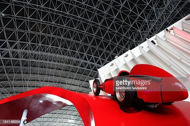 An old model Ferrari car decorates the entrance of the Ferrari theme park in the Emirati capital of Abu Dhabi on October 26 2010 'Ferrari World Abu...