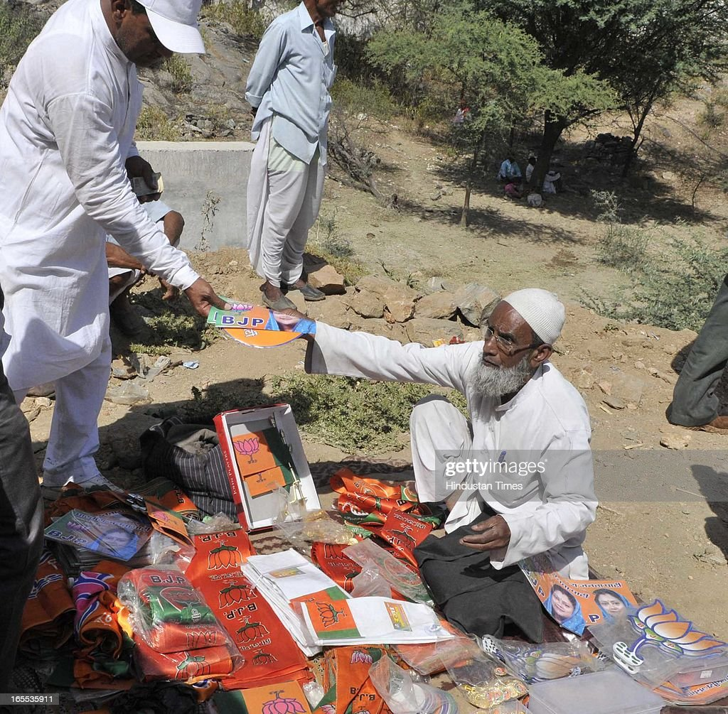 An old muslim man sells BJP's publicity material to Villager's during the rally at the start of Former Rajasthan CM and state BJP president Vasundhara Raje's Suraj Sankalp Yatra at Charbhuja village, on April 4, 2013 in Rajasamand, India. The Rajasthan assembly elections are due later this year.