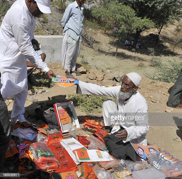 An old muslim man sells BJP's publicity material to Villager's during the rally at the start of Former Rajasthan CM and state BJP president...