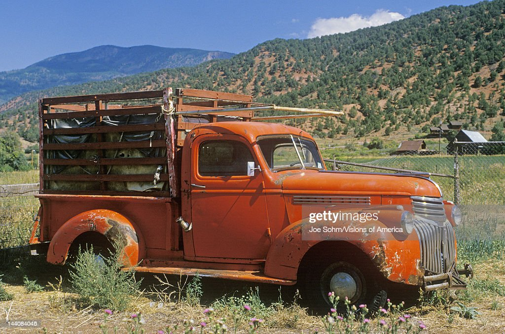 An old orange truck rests abandoned in a Colorado field Snowmass Colorado