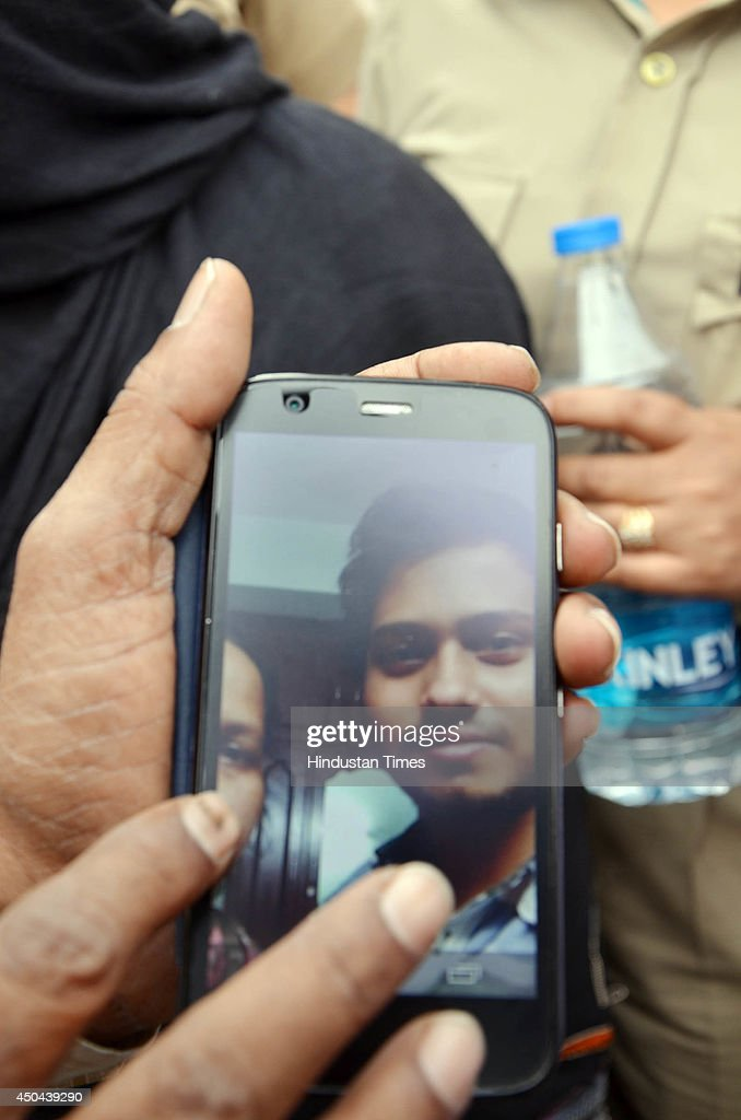 An old photo of Mohammad Shabir Hussain in Mobile of his mother which she showing media after she identified dead body of her son which was recovered from Beas river during search operation on June 11, 2014 in Mandi, India. The rescue team had recovered six bodies so far from the river. A wall of water washed away 24 engineering students and a tour operator Sunday evening after water was released into the river allegedly without a warning from a nearby Pandoh Dam on Beas River.