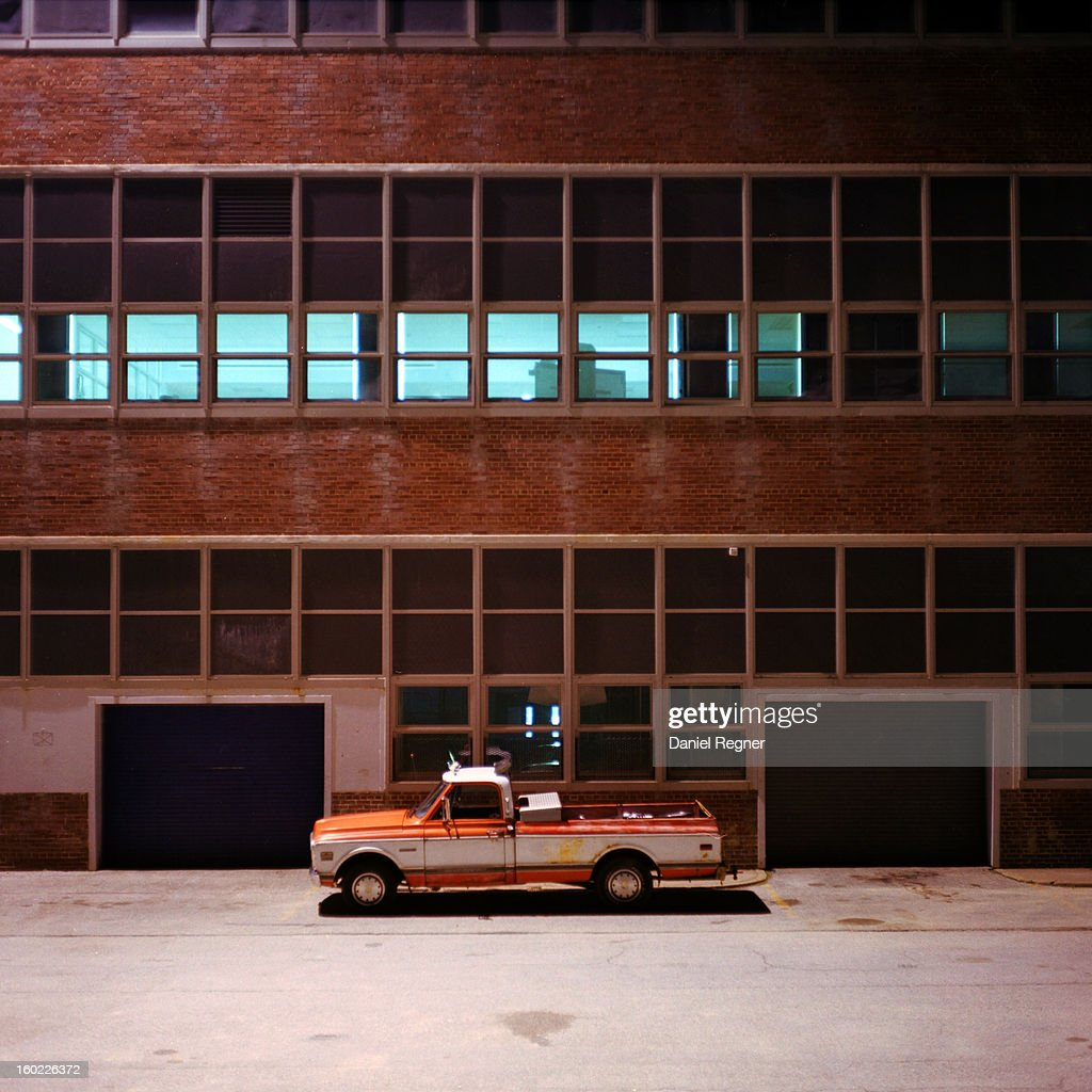 CONTENT] An old red truck is parked outside of a school at night, with all the windows lit up in a neat line of blue.