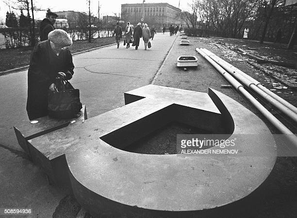 An old Russian woman fixing her belongings on a vandalized symbols of the Communism the Hammer and Sickle on an avenue of Moscow on November 1990 The...