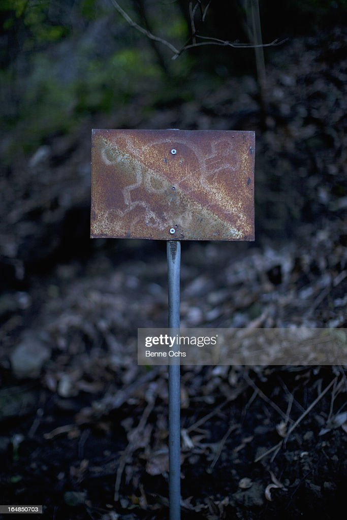 An old rusty sign with a skull and crossbones on it posted outdoors