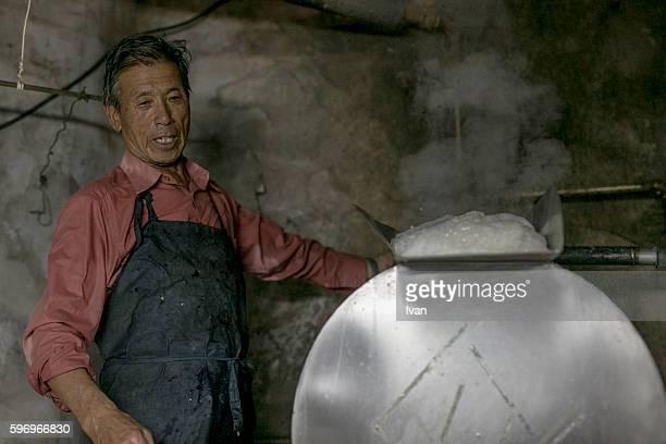 An Old Senior Asian Man Making Soy Milk and Tofu