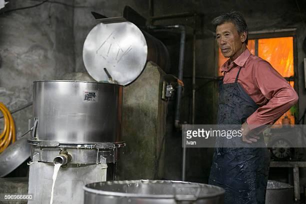 An Old Senior Asian Man Making Tofu and Soy Milk