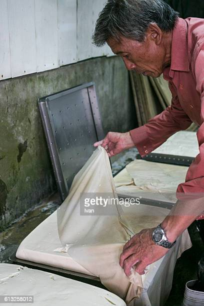 An Old Senior Asian Man Making Tofu