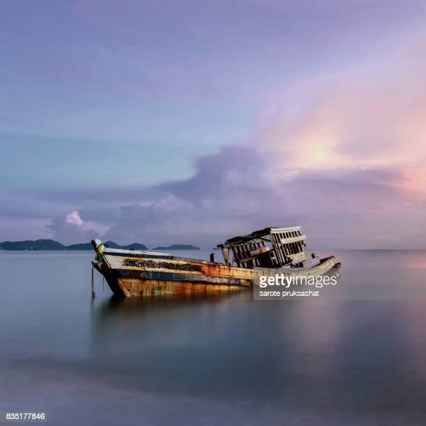 An old shipwreck ,Wrecked boat abandoned stand on beach or Shipwrecked off the coast of Thailand.