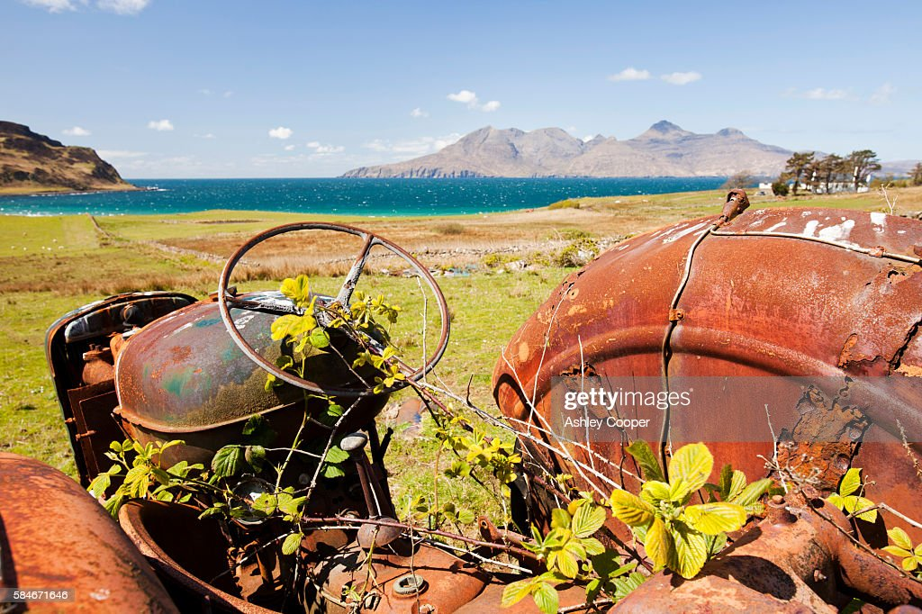 An old tractor abandoned at Cleadale on the Isle of Eigg, looking towards the Isle of Rhum, Scotland, UK.