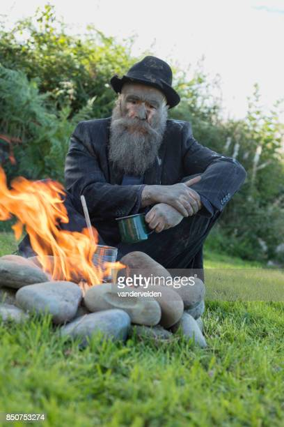 An old tramp warms himself by a camp fire