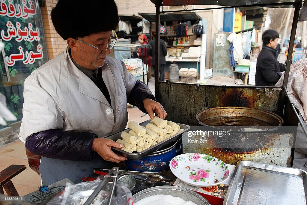 An old Uighur man makes snack at street in Kashgar, on December 10, 2012 in Kashi, China. Kashgar is home to the ethnic Uyghur Muslim community.