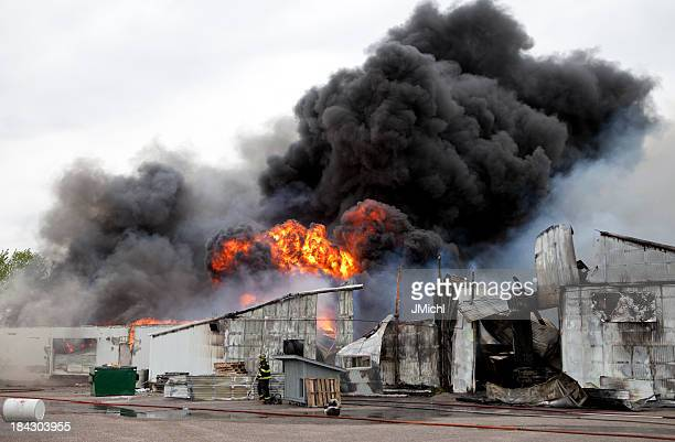 An old warehouse on fire with black smoke
