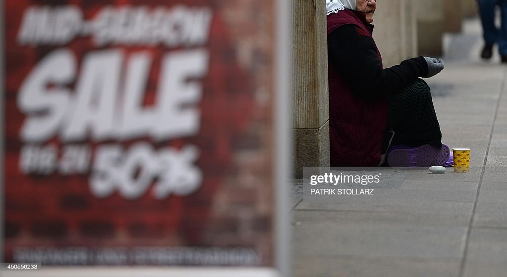 An old woman begs for money near a poster announcing Sales on a shopping street on November 19, 2013 in Dortmund western Germany. STOLLARZ