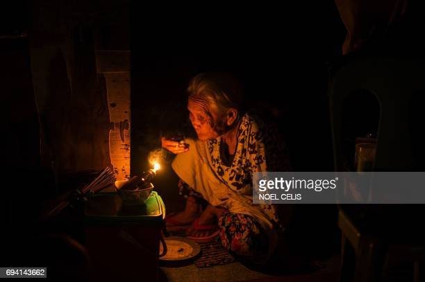 TOPSHOT An old woman eats her Iftar the evening meal when Muslims end their daily Ramadan fast at sunset without electricity on the southern...