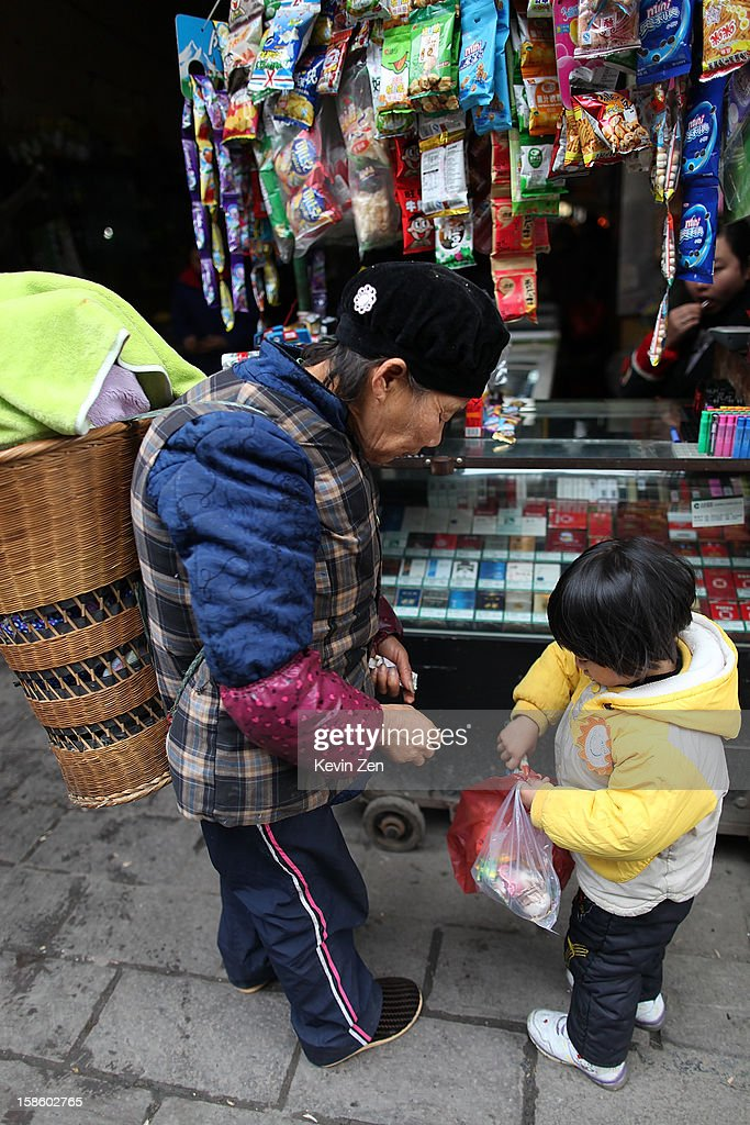 An old woman goes shopping in a store with her Granddaughter on December 18, 2012 in Fenghuang, China. Fenghuang Town was built by Emperor Kangxi in 1704 and after 300 years, the city's ancient appearance has been well preserved. Hunan is located in southwest Hunan Provience of China with a population of 370,000 within a total area of 1700 square kilometers.