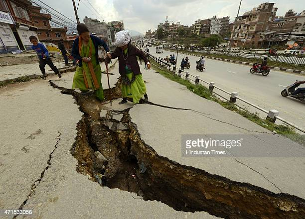 An old woman is assisted as she tries to cross a massive crack in the road damaged by earthquake on April 29 2015 in Kathmandu Nepal Last week's...