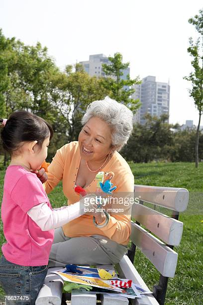 An old woman is playing with a girl.
