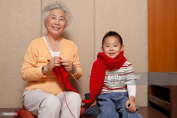 An old woman knitting a scarf for her grandson celebrates Chinese New Year.