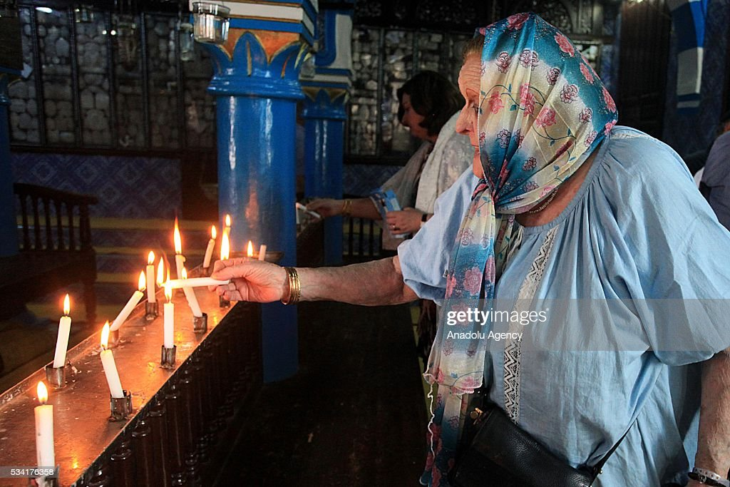 An old woman lights a candle as Jews from different countries visit Synagogue La ghriba to celebrate Lag BaOmer in Djerba, Tunisia on May 25, 2016.