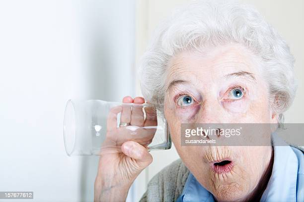 An old woman looking shocked with a glass on her ear