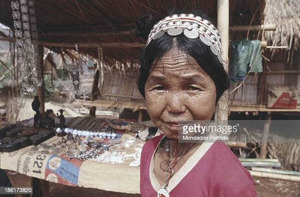 An old woman of the Yao's tribe in front of a exposure of local crafts in a hut of the village The Yao'sTribe lives in the north of Thailand in an...