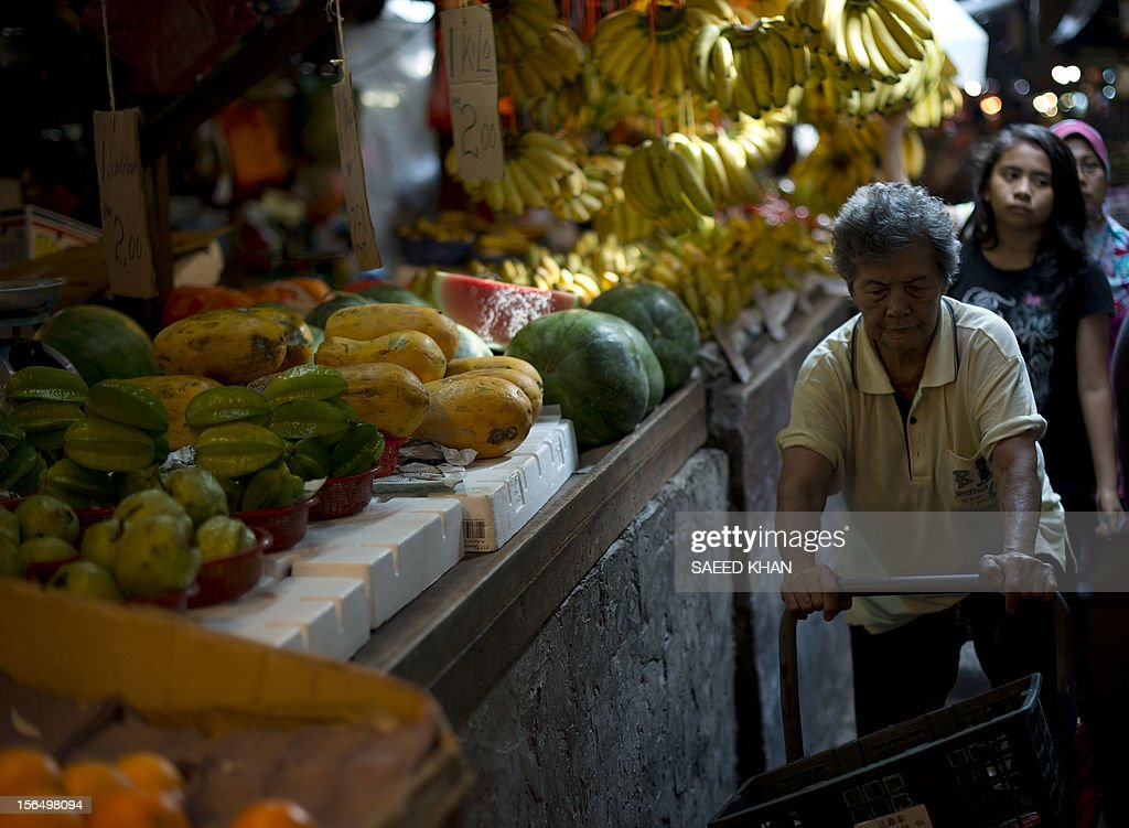 An old woman pushes a cart through fruit stalls at a vegetable market in down town Kuala Lumpur on November 16, 2012. The State bank of Malaysia announced that the economy expanded by 5.2 percent in the third quarter. AFP PHOTO / Saeed KHAN